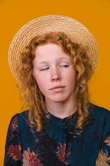 色付きの背景を持つスタジオで興味のある巻き毛の女性