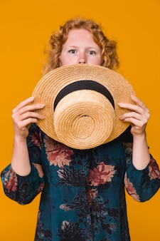 驚きの若い女性が帽子で顔を覆っている