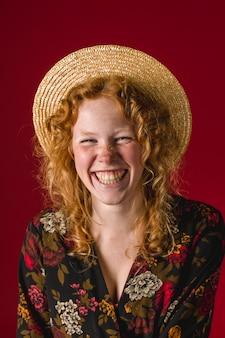 カメラで笑って帽子の赤毛の若い女性