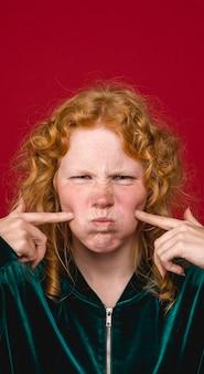 面白い若い生姜女性の顔をゆがめた