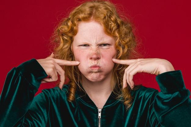 陽気な若い女性が吹いて頬を押す