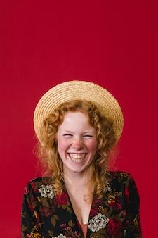 笑って麦わら帽子をかぶっている幸せな若い生姜女