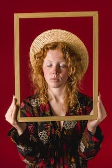 Рыжая молодая женщина держит рамку с закрытыми глазами