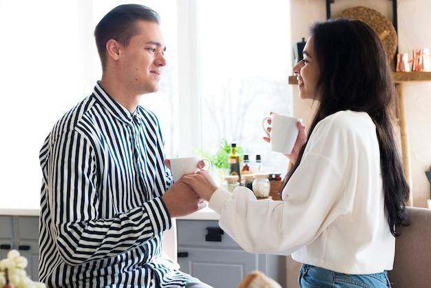 Молодые счастливые любовники держатся за руки и смеются