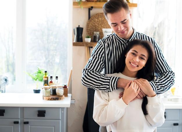 若いカップルが台所に座っていると抱きしめる