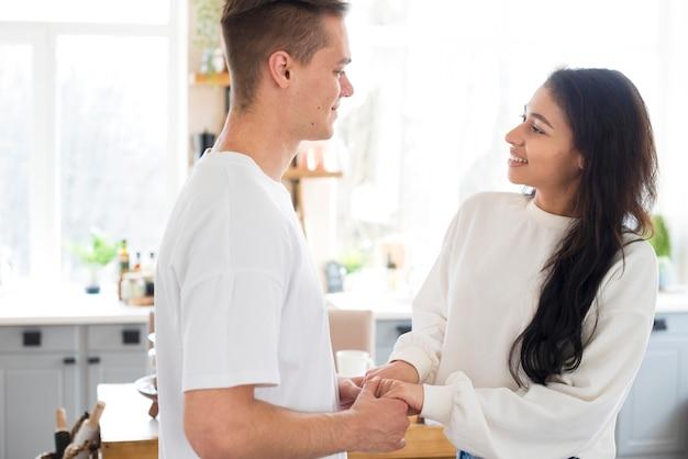 腕を繋いでいる多民族の若いカップル