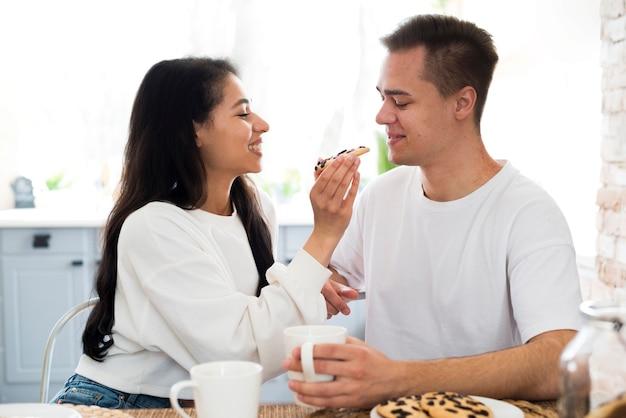 Этническая самка кормит с печеньем парня