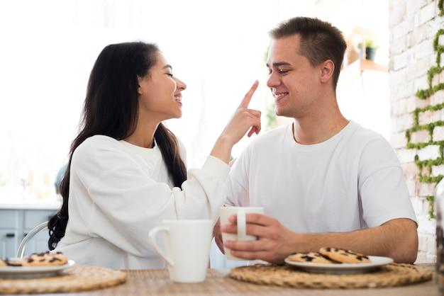 民族の女性が彼氏の手で鼻に触れる
