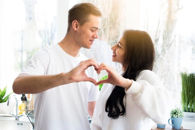 お互いを見て愛のジェスチャーを作る多民族カップル