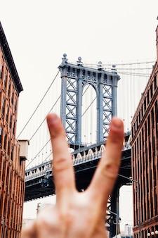 Человек показывает знак мира на фоне моста