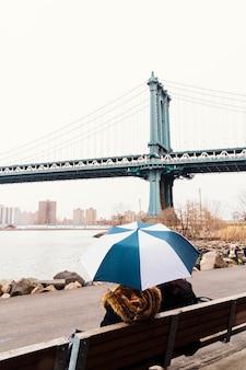 橋の眺めを楽しむ傘を持つ人