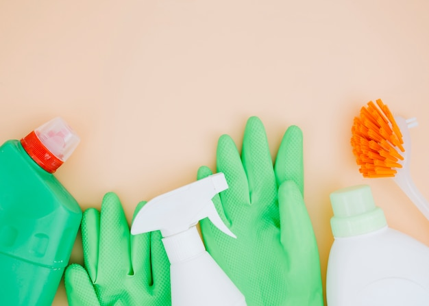 Зеленый аэрозольный баллончик и перчатки с чистящим моющим средством с кисточкой на бежевом фоне
