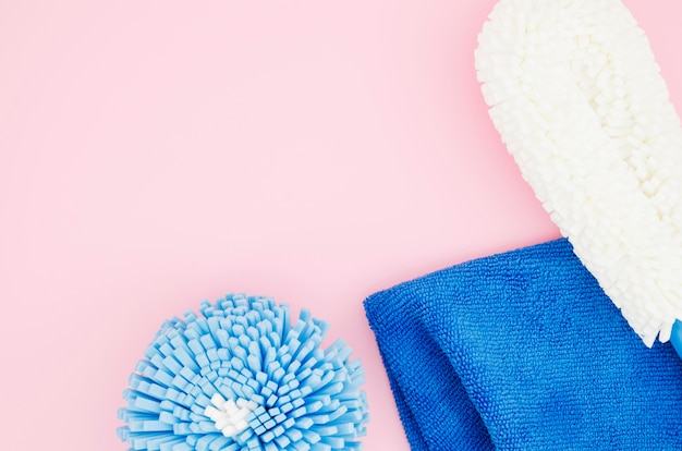 Различные виды чистящих губок с синей салфеткой на розовом фоне
