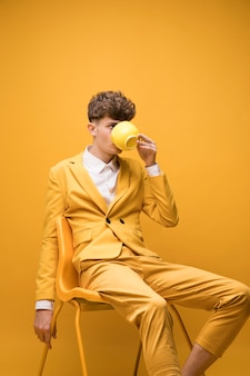 Портрет модного мальчика, пьющего из чашки