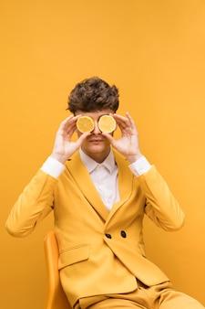 目の前にレモンスライスと黄色のシーンで若い男の肖像