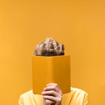 黄色のシーンで本を読んで若いハンサムな男