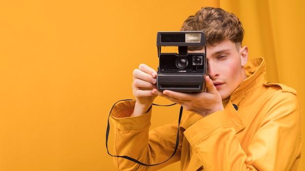 黄色のシーンでレトロなカメラを持つ男