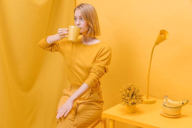 Современная женщина пьет из кружки