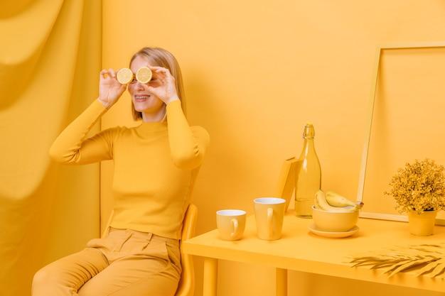 黄色のシーンで目の前にレモンを保持している女性