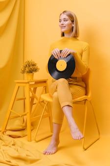 黄色のシーンでビニールを保持している女性の肖像画