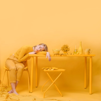 黄色のシーンでテーブルで寝ている女性