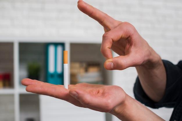 彼の指を通してタバコを打つ男のクローズアップ