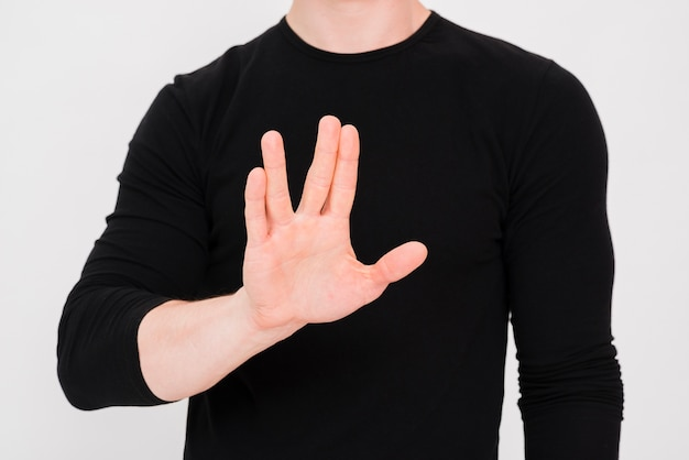 白い背景に対して停止ジェスチャーを示す人間の手