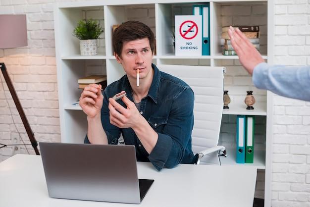 女性同僚のオフィスで実業家照明タバコに一時停止の標識を表示