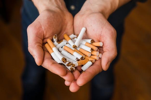 Крупный план мужской руки с кучей ломающихся сигарет
