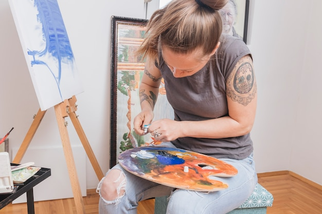 入れ墨の女性がパレットに塗料を混合