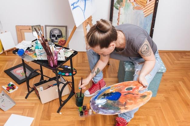 入れ墨の女性がパレットを押しながら絵筆を水に浸す