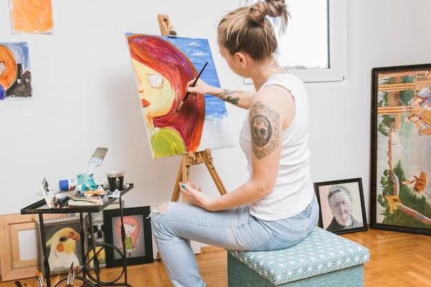 Художник рисует картину в мастерской