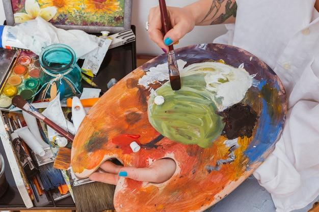 パレットの色を混ぜる画家