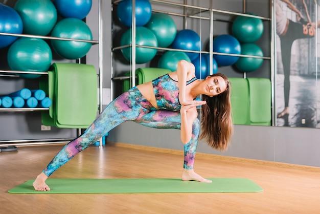 Женщина делает йога позиции в фитнес-центре