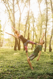 健康な男性と女性の公園でアクロヨガを行う