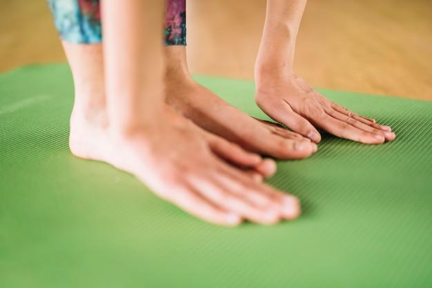 Конец-вверх ног и рук женщины практикует йогу на зеленой циновке