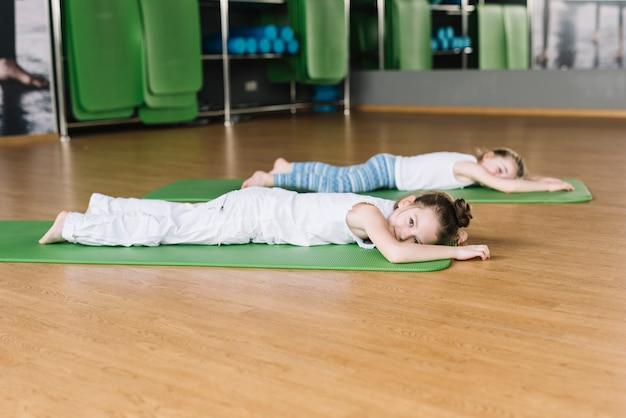 Маленькая девочка отдыхает на коврике после тренировки
