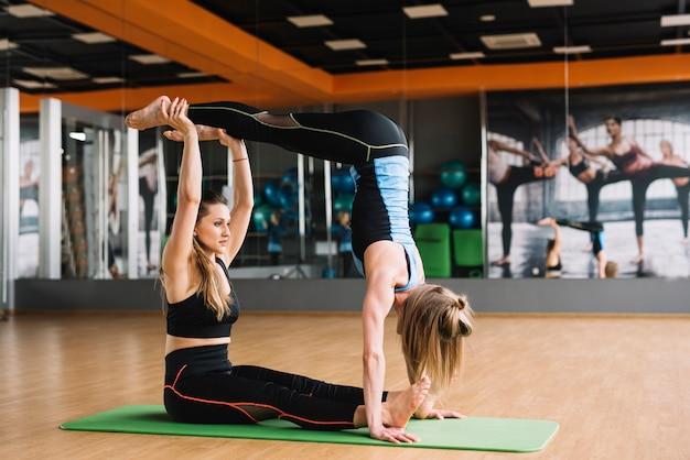 Две красивые молодые и активные женщины в спортивной одежде растягиваются в тренажерном зале