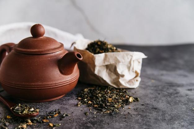 Глиняный чайник и сухие листья на бетоне
