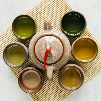 Керамические чайные чашки в окружении чайника на подставке для столовых приборов на бетонном фоне