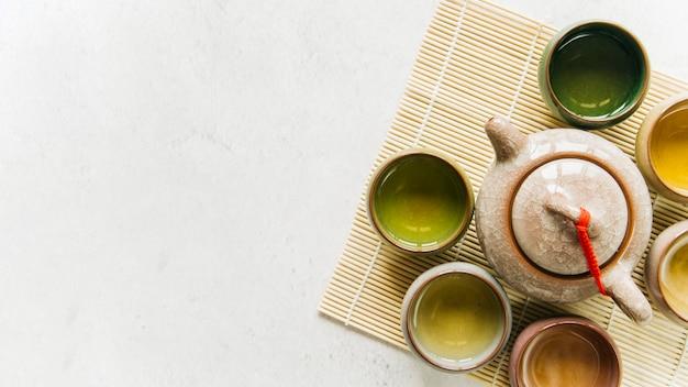 Травяные чашки в окружении чайников на белом фоне