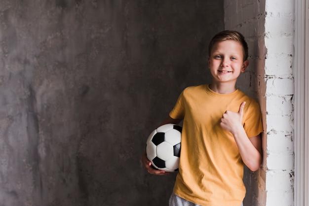 Портрет улыбающегося мальчика перед бетонной стеной, держа футбольный мяч, показывает палец вверх