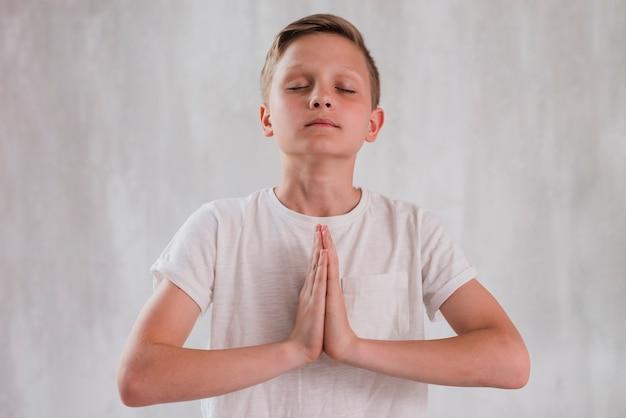 Крупным планом мальчика, закрыв глаза, делает медитации против бетонной стены