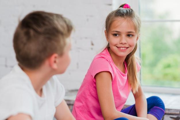 Портрет улыбающейся девушки, смотрящей на мальчика