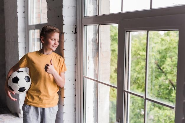 Улыбающийся мальчик держит футбольный мяч, глядя через окно