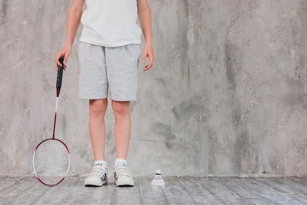 Низкая часть мальчика, стоящего с ракеткой и воланом