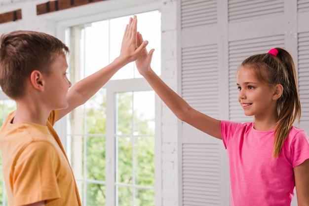 Улыбающийся мальчик и девочка, давая высокие пять у окна
