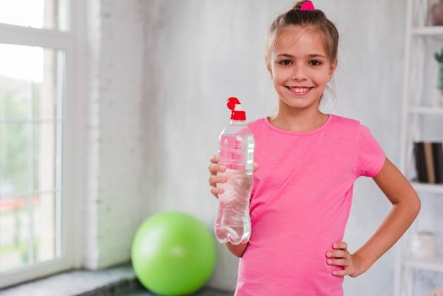 プラスチック製の水のボトルを手で押し微笑んでいる女の子の肖像画