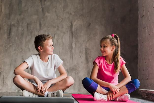 コンクリートの壁に対してカメラを見て彼の組んだ足で運動マットの上に座っている若いカップル