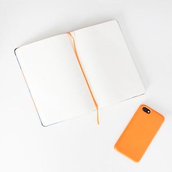 スマートフォンの横にある本を開く